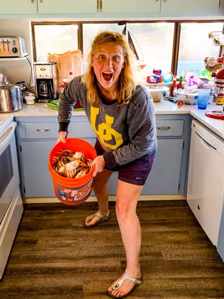 Woman holding a bucket of crab in a kitchen