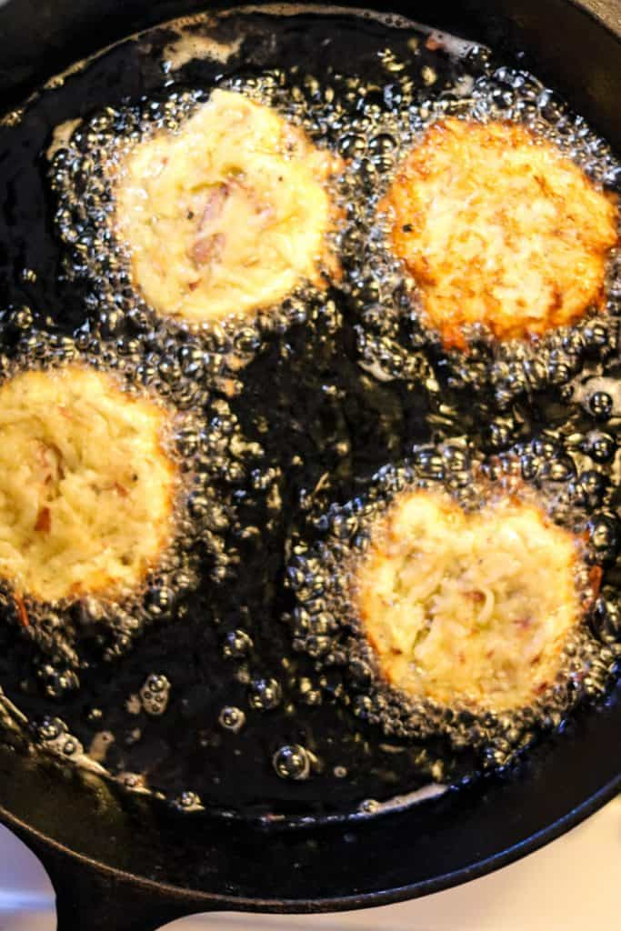 Latkes frying in hot oil in a cast-iron pan, shot from over head