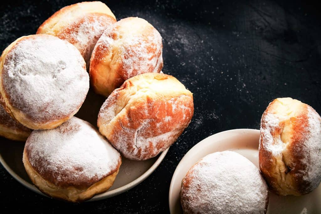 low angle shot of Israeli donuts or sufganiyot with powdered sugar on top.