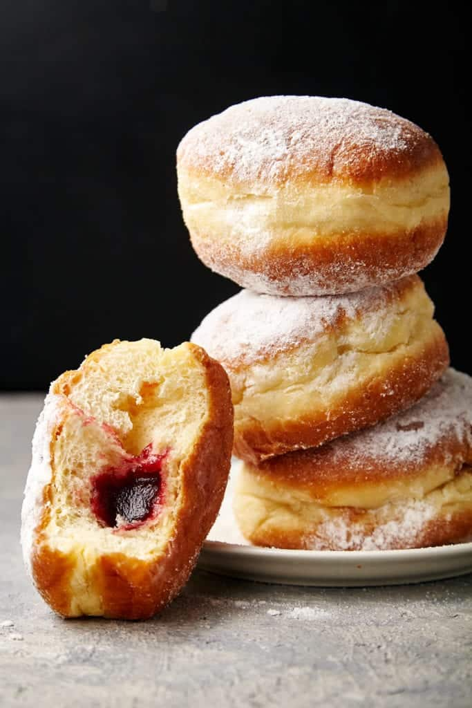 Sufganiyot or Israeli jelly donuts for hannukah dusted with powdered sugar. This is a low-angle shot that shows 3 donuts stacked on a white plate iwth one donot leaning against the stack that has a bite taken out of it so that you can see the jelly filling.