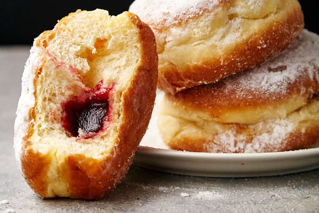 close up head-on photo of sufganiyot or Israeli jelly donuts.