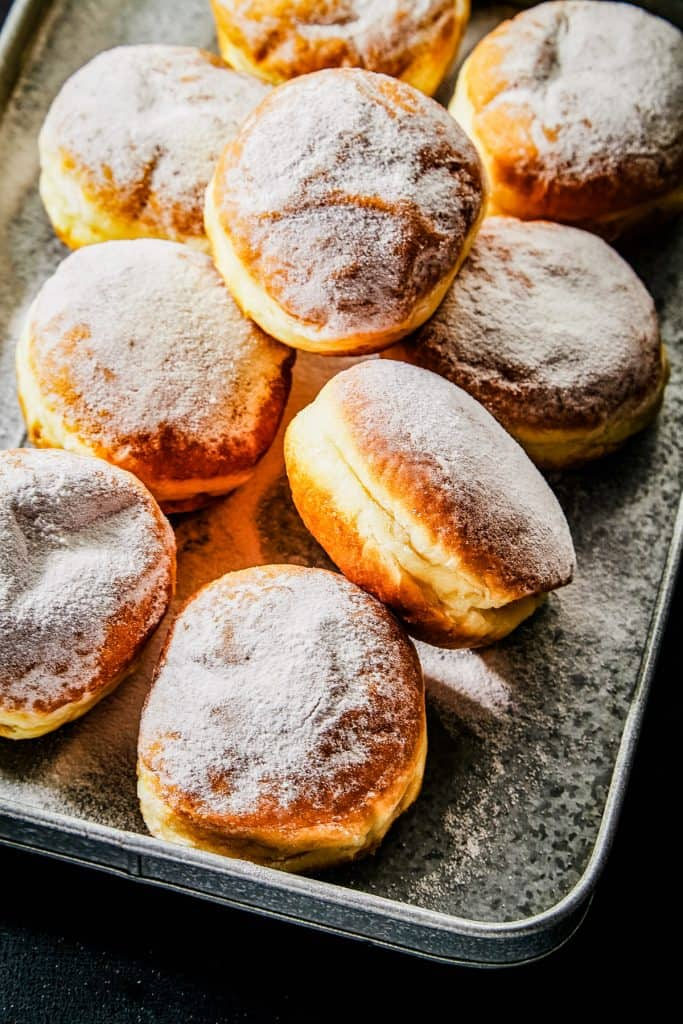 Low angle shot of sufganiyot or Israeli donuts dusted with powdered sugar. The donuts are piled on a baking sheet.