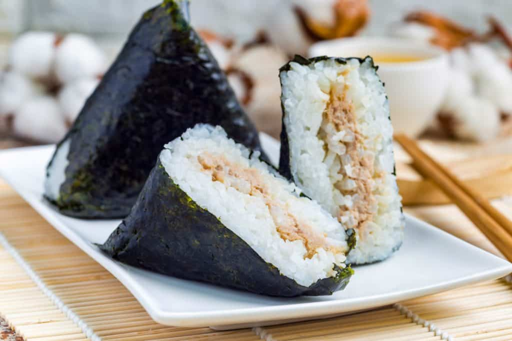 low angle shot of onigiri japanese rice triangle. One triangle is whole wrapped in seaweed. The other is cut in half so that you can see the inside. They are on a white plate on a bamboo mat.