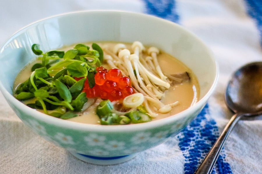 chawanmushi in a bowl topped with enoki mushrooms, salmon roe or ikura, pea sprouts, and scallions