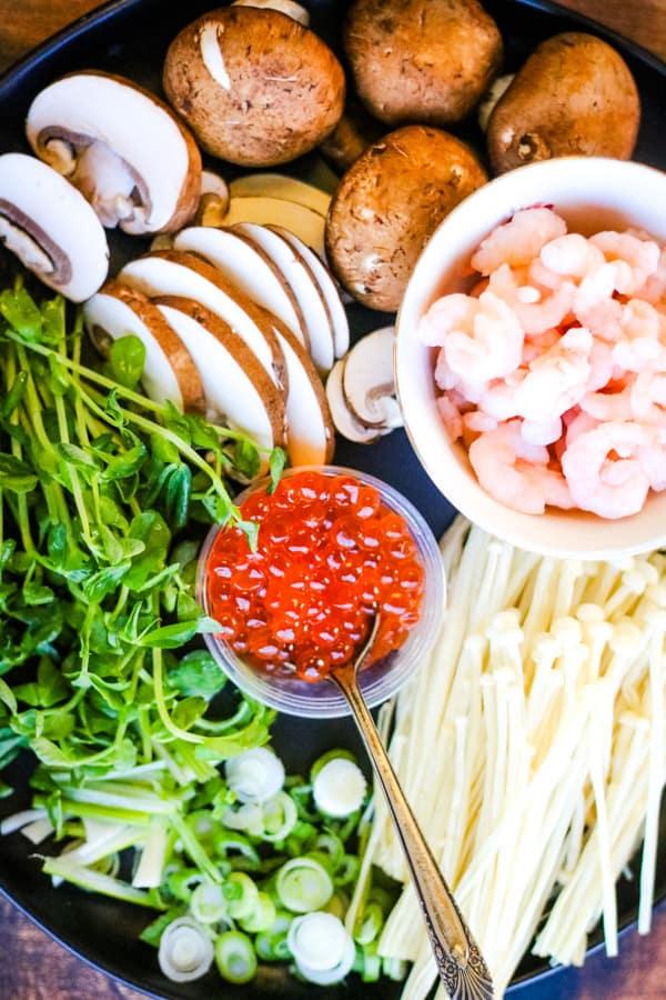 ingredients for chawan mushi including ikura salmon roe, enoki mushrooms, shiitake mushrooms, pea sprouts, scallions, baby shrimp