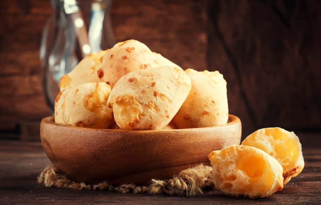 brazilian cheese bread in a wooden bowl shot from a low angle