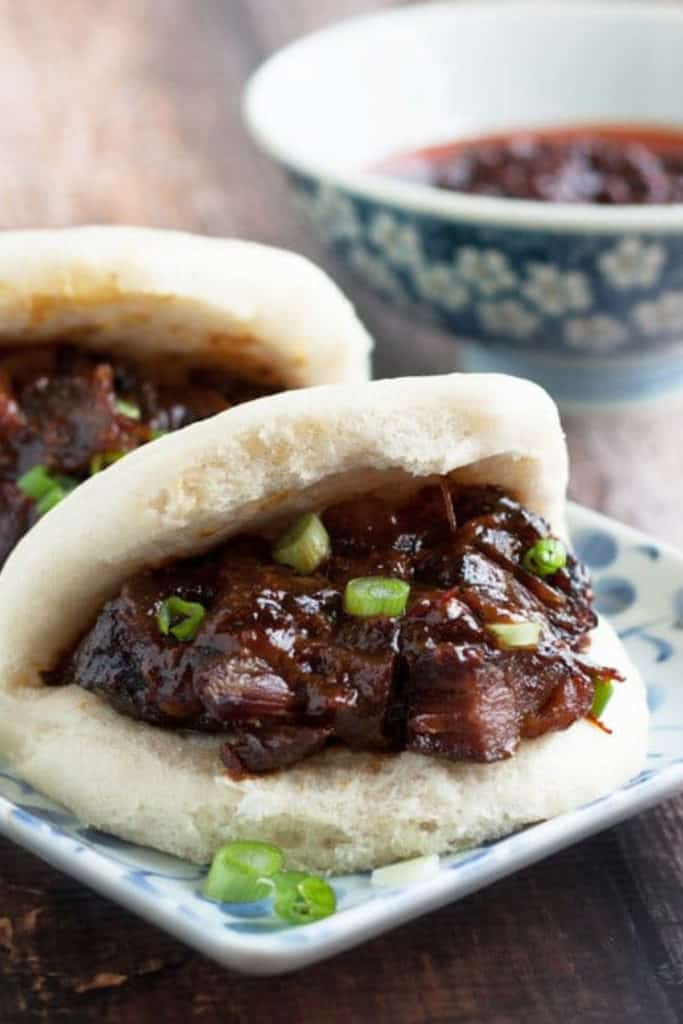 A low-angle shot of char siu pork stuffed in a steamed bun.
