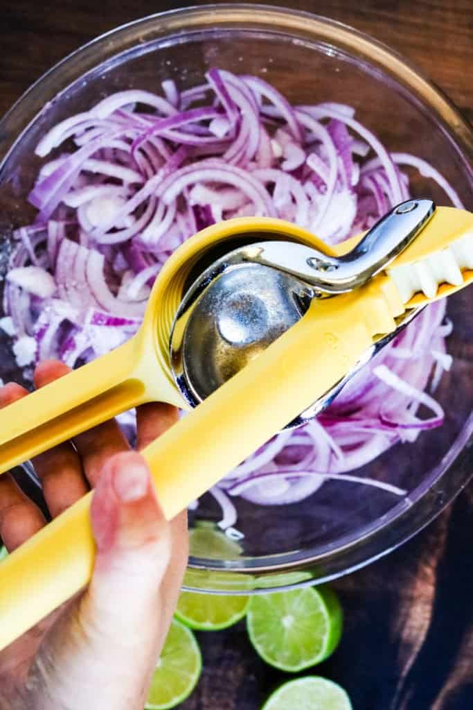 Squeezing lime juice over red onions to make Mexican pickled onions