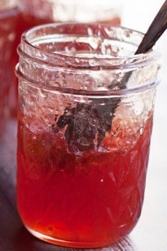 A close up side shot of a jar of quince jelly with a wooden spoon in it.