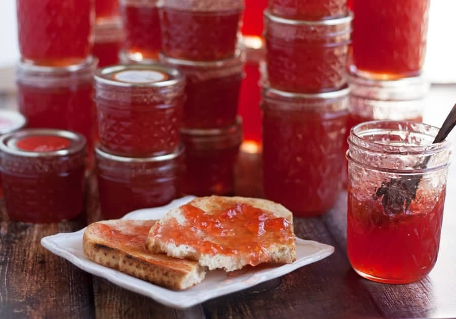 Jars of quince jelly and a piece of toast on a plate with quince jelly spread on top