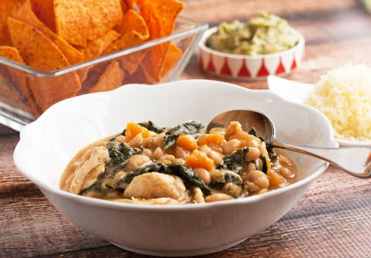 white bean chicken chili in a bowl with garnishes
