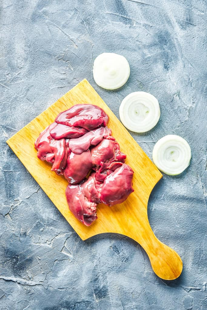 Raw chicken livers on a cutting board with onion slices.