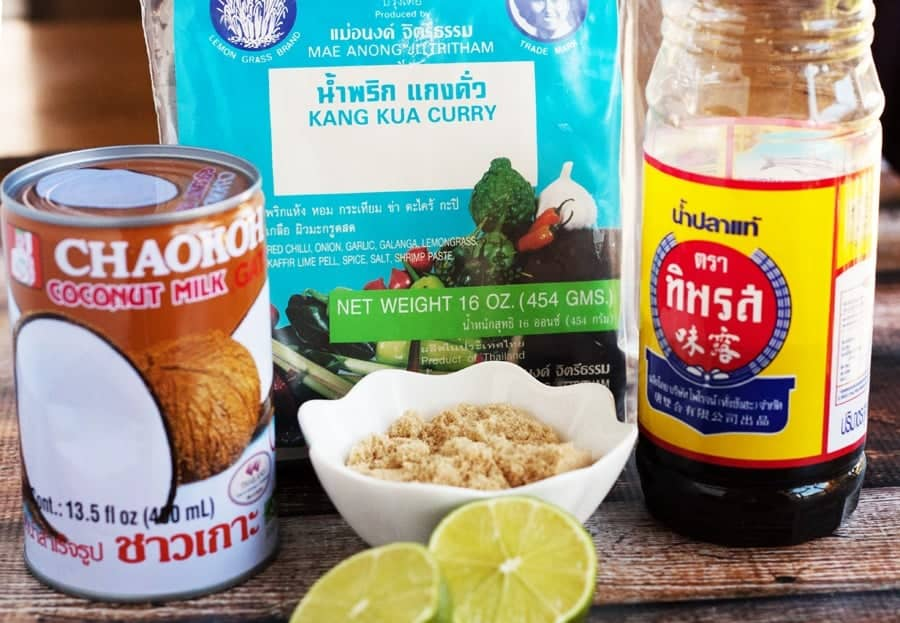 thai peanut sauce ingredients including coconut milk, fish sauce, curry paste, brown sugar, and limes