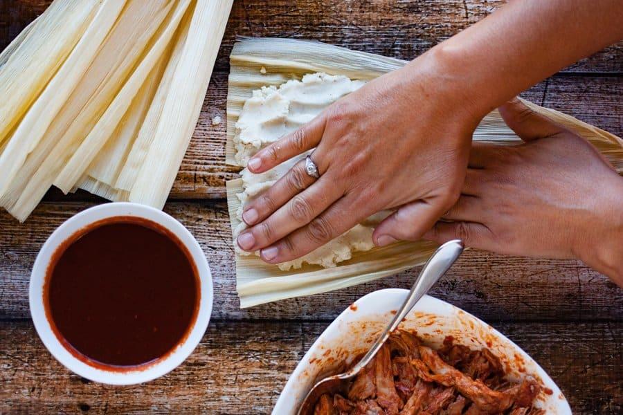 spreading tamale dough on corn husk