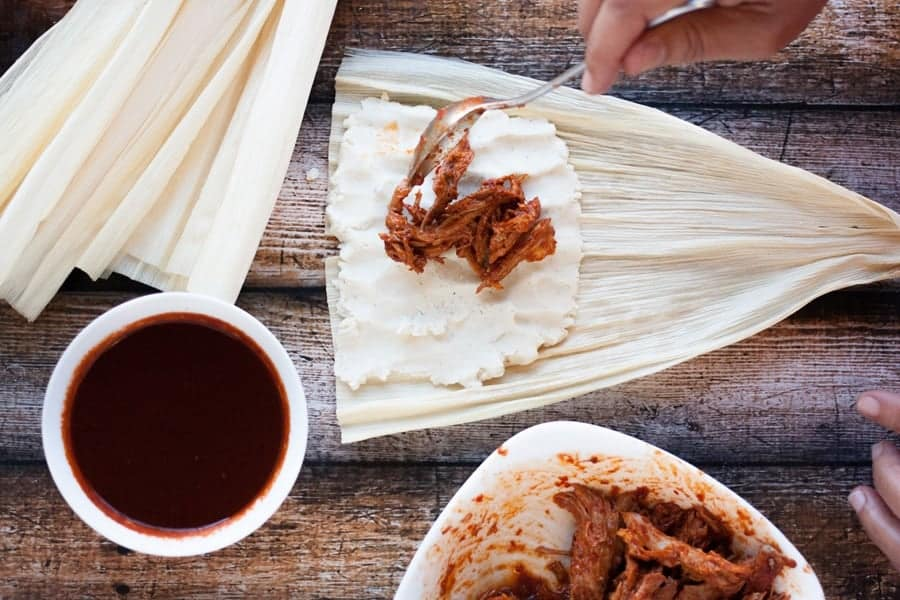 filling homemade tamales with pork in red chile sauce