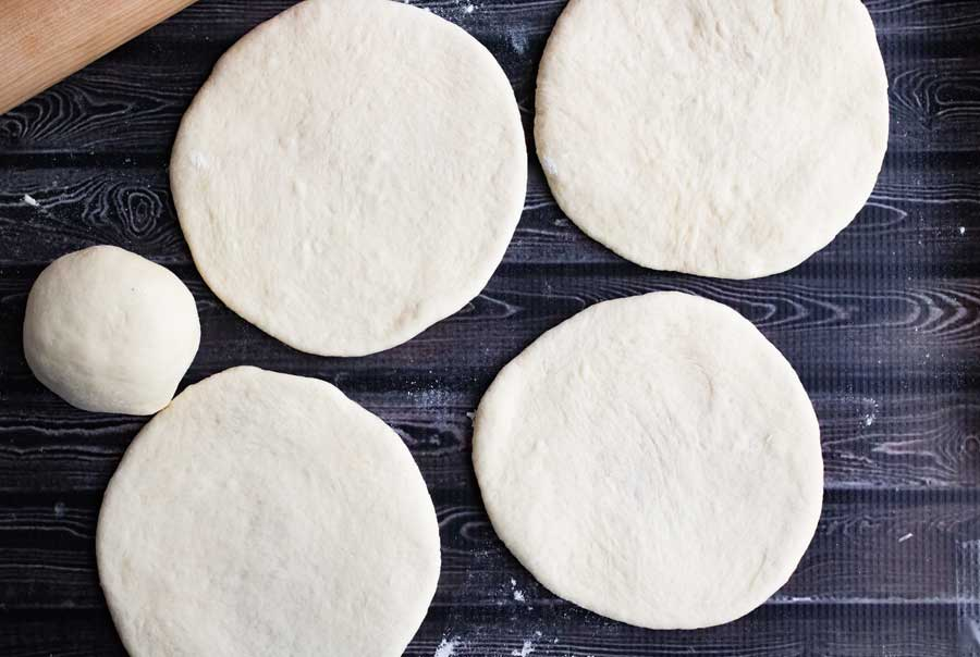 homemade pita dough rolled out into flat rounds for baking