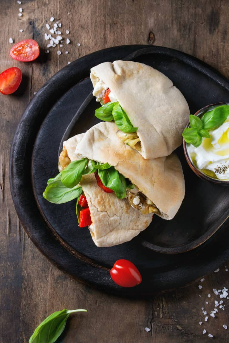 overhead shot of 2 halves of pita bread stuffed iwth eggplant, roasted pepper and fresh basil.