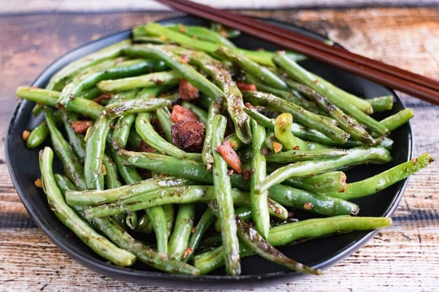 chinese dry fried green beans on a plate with chopsticks