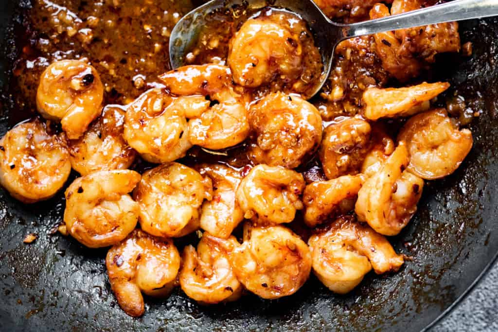 A photograph of cooked Szechuan shrimp in a skillet.