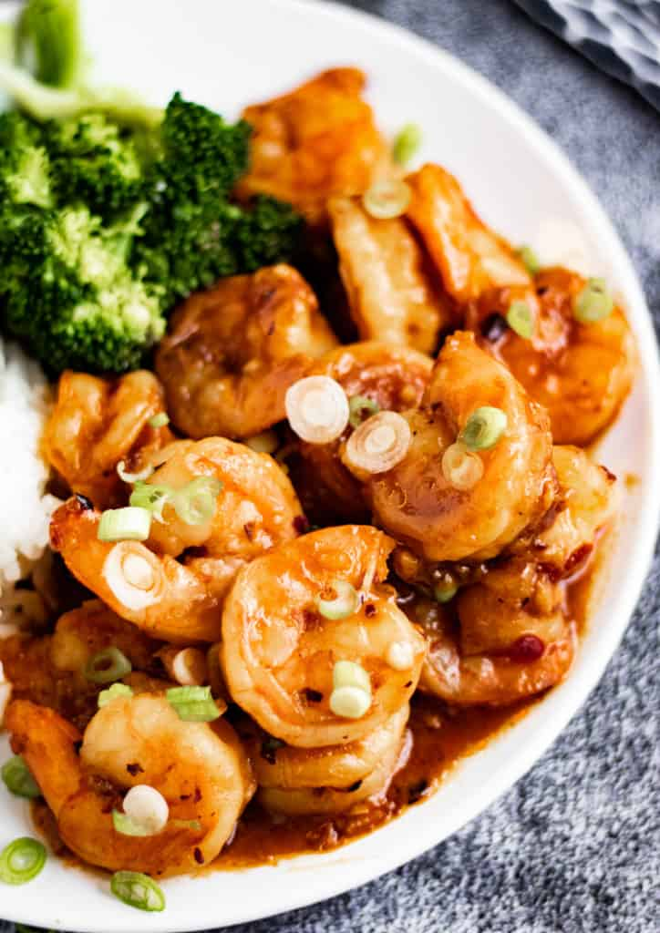 The shrimp on a white plate with steamed rice and broccoli, shot from a low angle.
