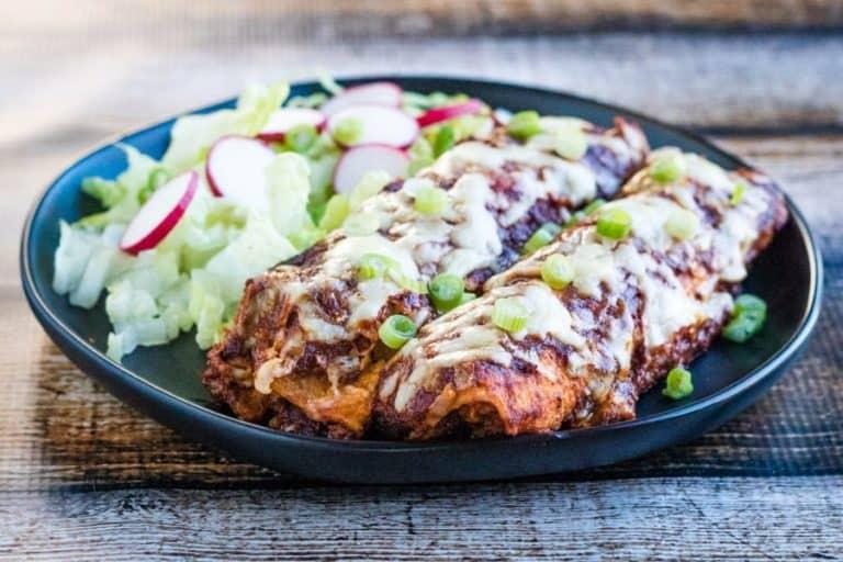 chicken enchiladas with salad on plate