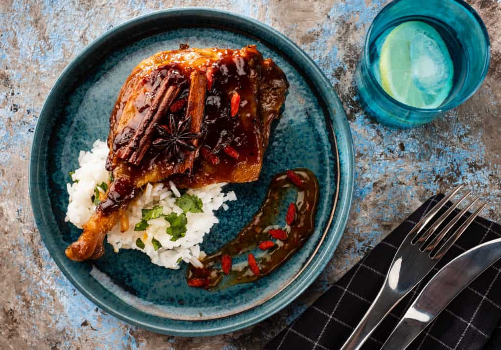 Overhead shot of instant pot duck confit, seared and topped with spiced pomegranate glaze