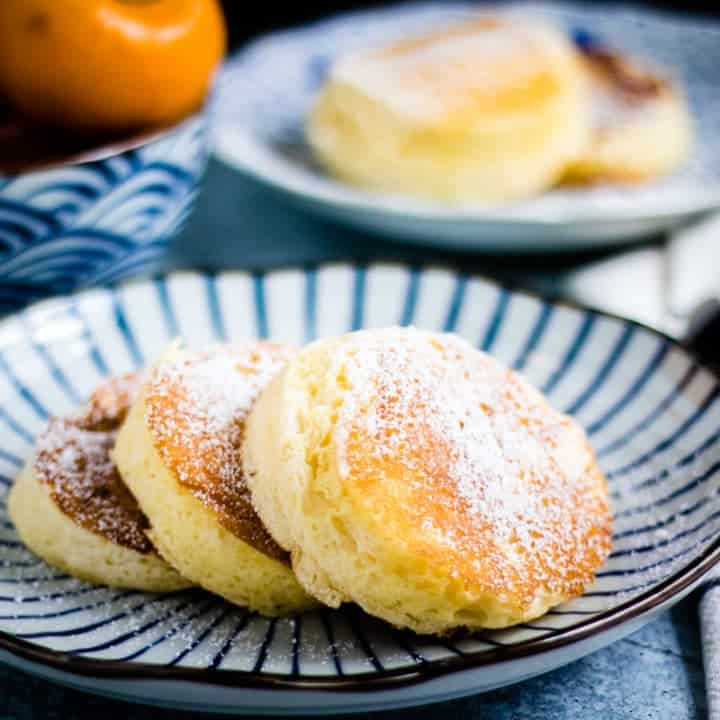 three japanese pancakes, dusted with powdered sugar, on a japanese plate. they look delicious