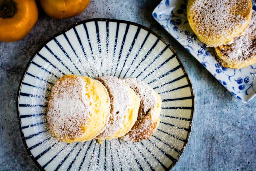 overhead shot of japanese souffle pancakes on a pretty japanese plate with fuyu persimmons