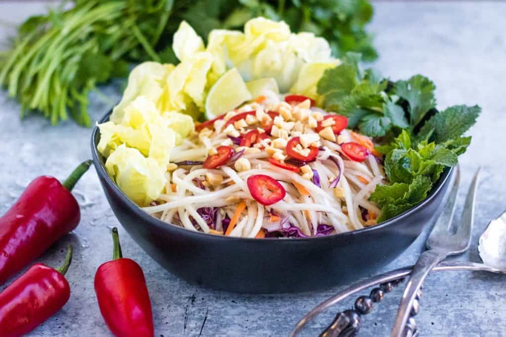 shredded green papaya, carrots, red and red cabbage in a bowl topped with red chiles and peanuts