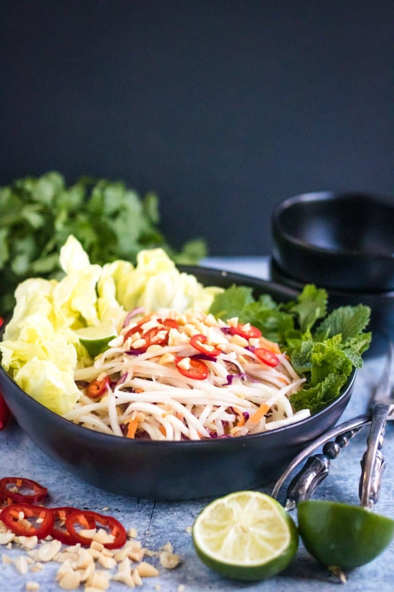 A bowl of green papaya salad with a black backgrond