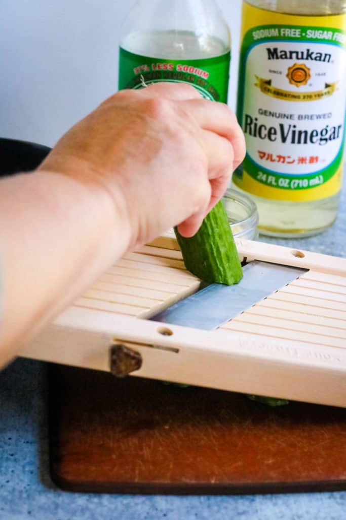 Slicing cucumbers on a mandoline for Japanese cucumber salad