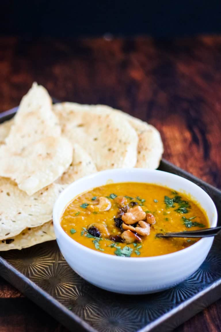instant pot mulligatawny soup in a bowl on a metal tray with papadums on the side