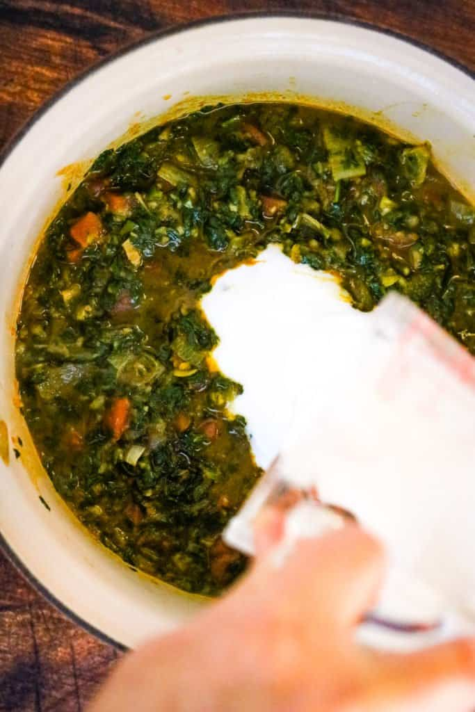 Adding coconut milk to the spinach-curry mixture for palak paneer