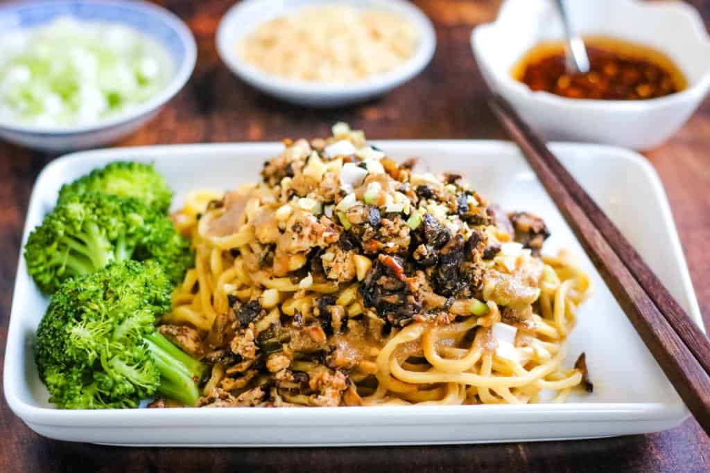 Vegetarian dan dan noodles ready to eat on a plate with broccoli