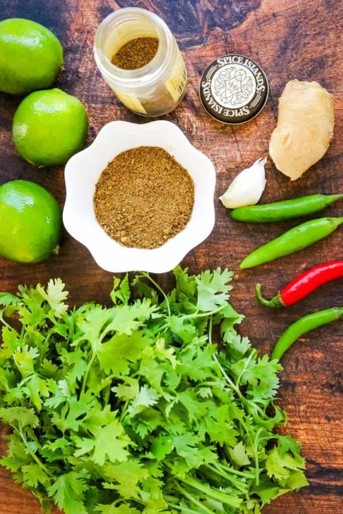 Ingredients for cilantro yogurt chutney including cilantro, garam masala, chilies, limes, and garlic