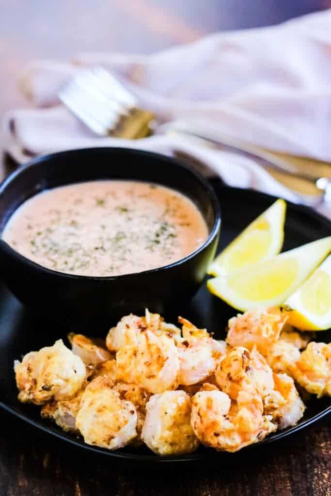 bang bang shrimp on a black plate with a bowl of bang bang dipping sauce and lemon wedges