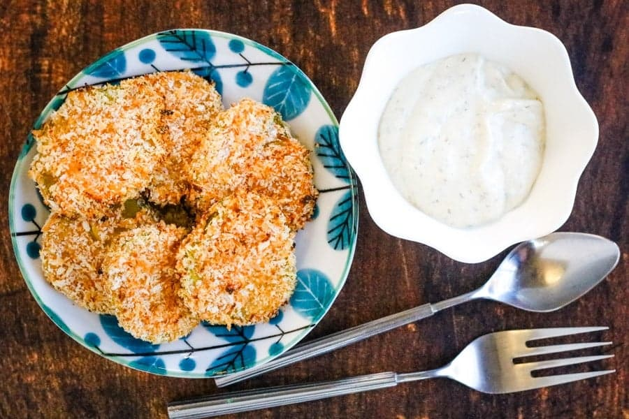 Air fryer fried pickles on a plate with turquoise leaves with a bowl of ranch dressing for dipping