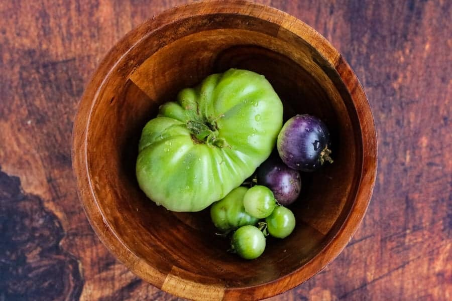 green or unripe tomatoes in a wooden bowl