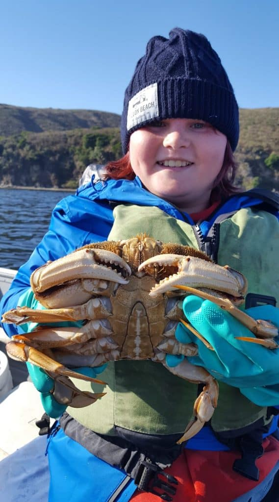 Boy with a big dungeness crab in a boat