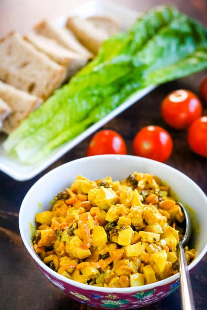 Curry chicken salad in a bowl iwth bread, lettuce, and cherry tomatoes