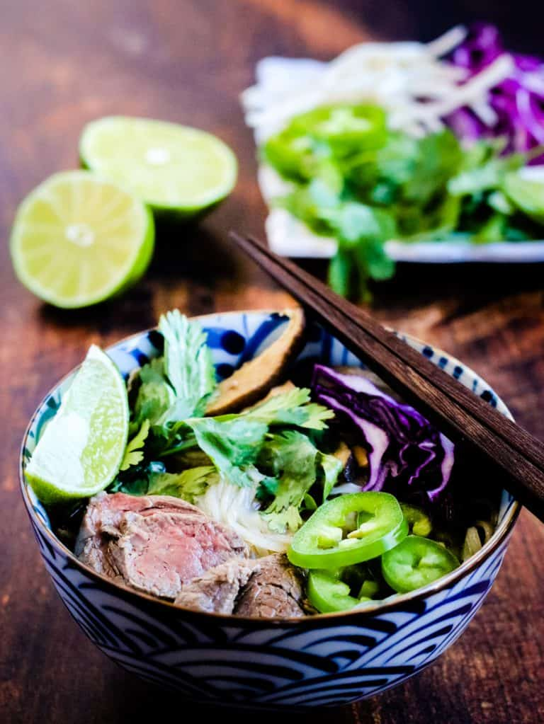 low angle photo of a bowl of beef pho with garnishes