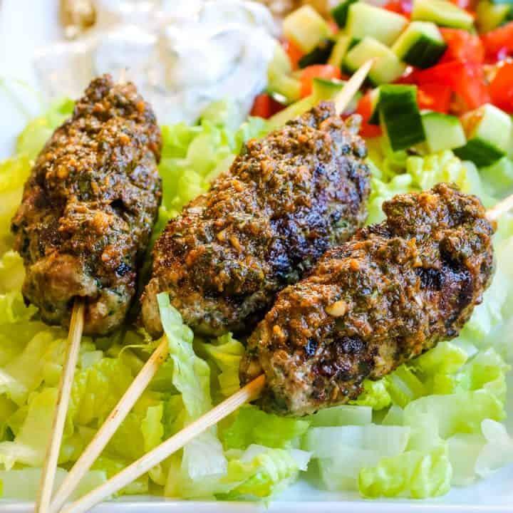 lamb kofta kebabs with charmoula sauce on a bed of lettuce