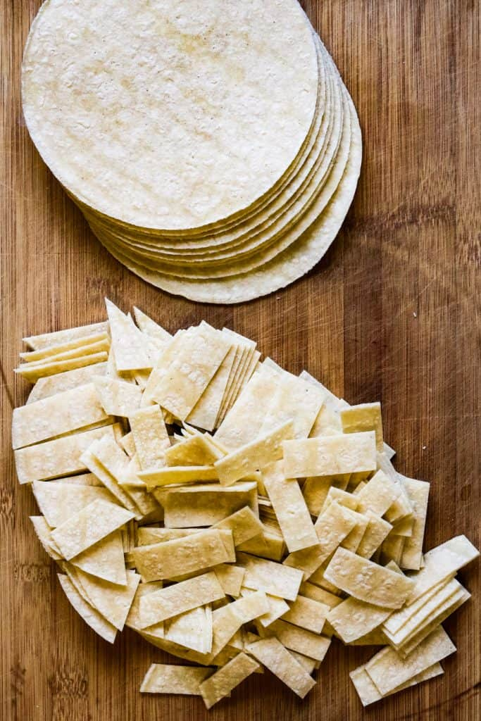stack of corn tortillas and corn tortillas cut into strips on a cutting board