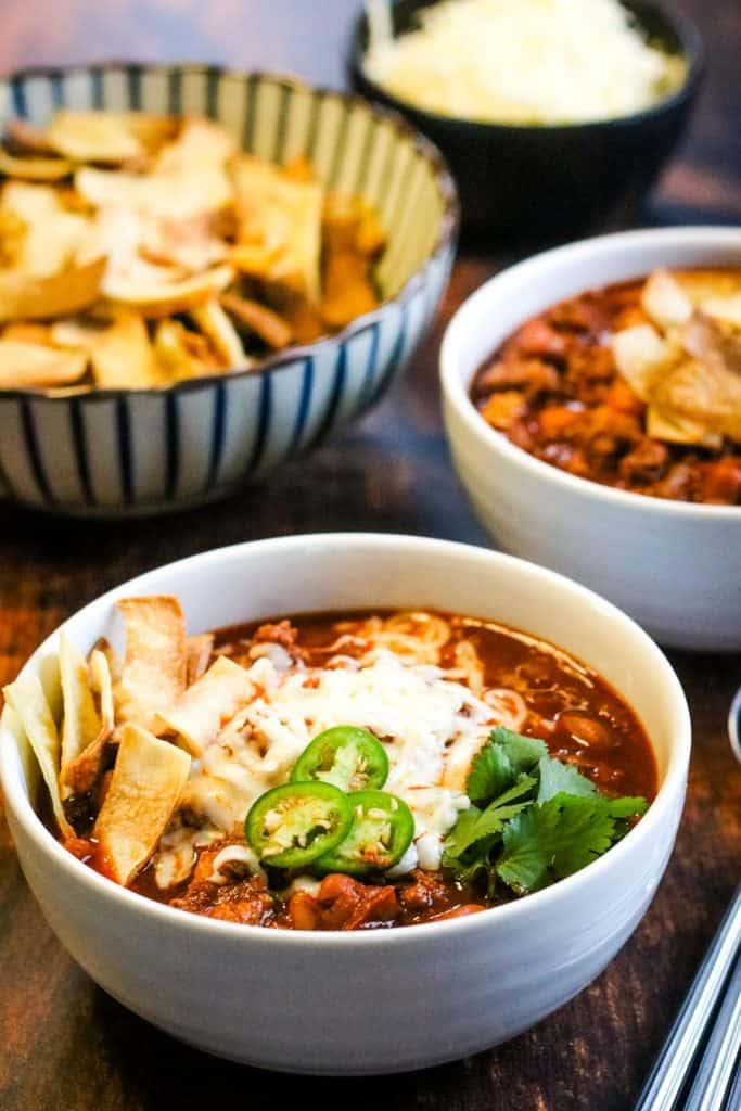 low angle shot of chili in bowls with toasted tortilla strips, sliced jalapenos, shredded cheese, adn cilantro