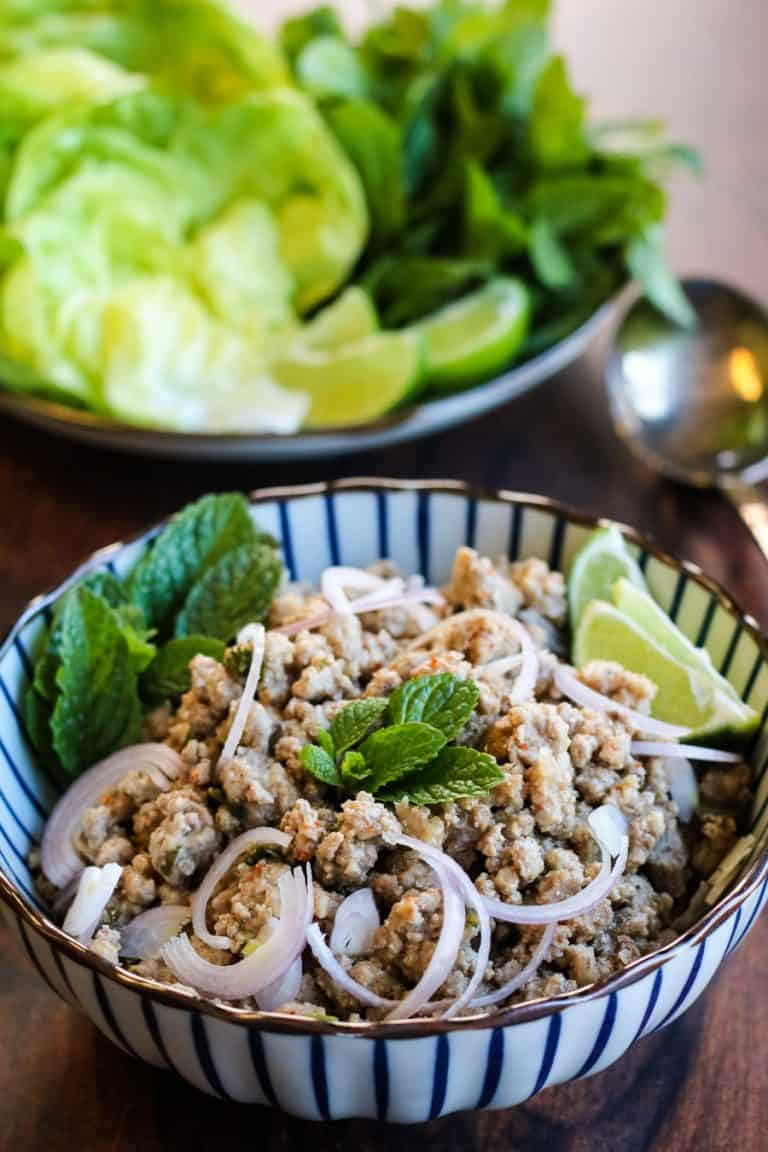 Low angle shot of thai larb with garnishes of fresh mint, lime wedges, sliced shallots and lettuce