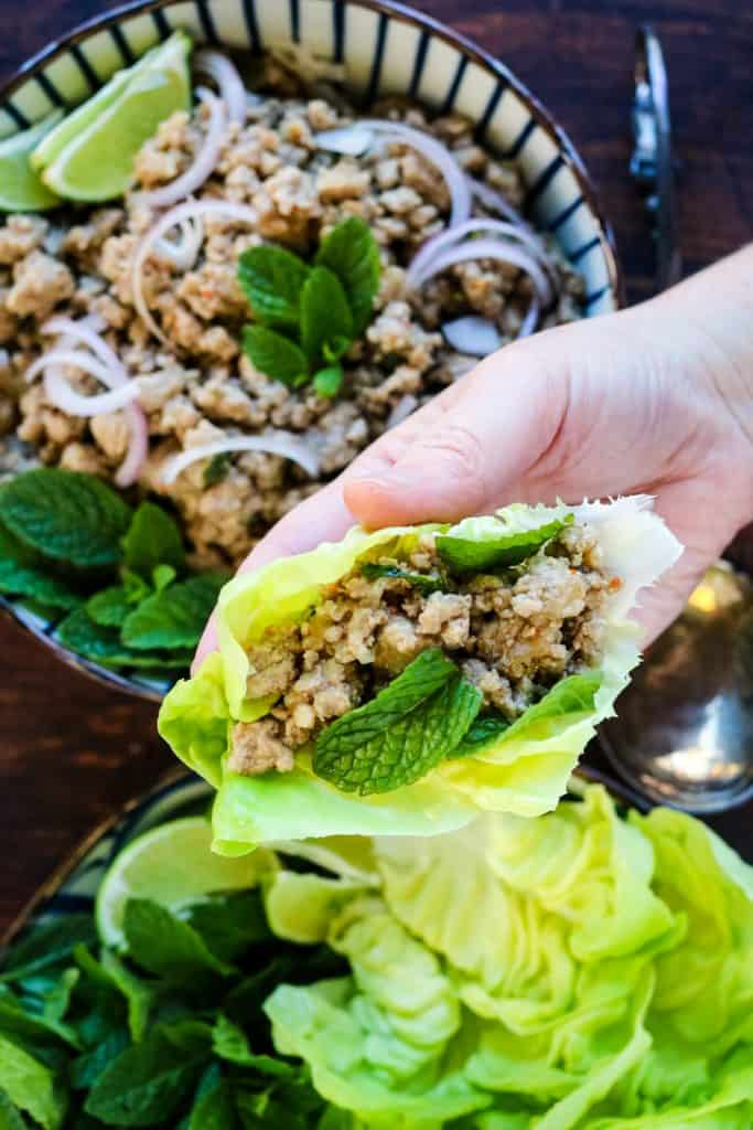 larb wrapped up in a lettuce leaf with fresh mint leaves