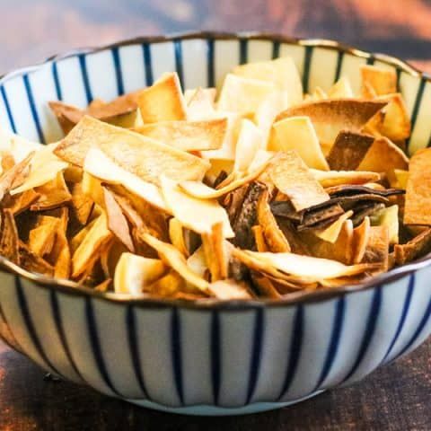 baked tortilla strips in a blue-and-white striped bowl