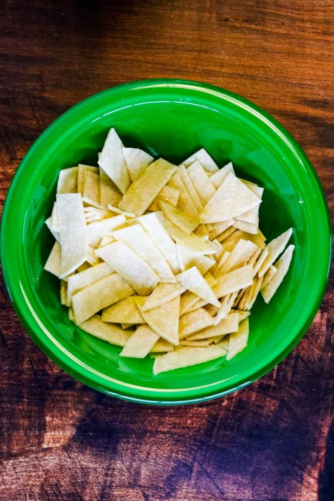 corn tortilla strips in a bowl with olive oil and salt