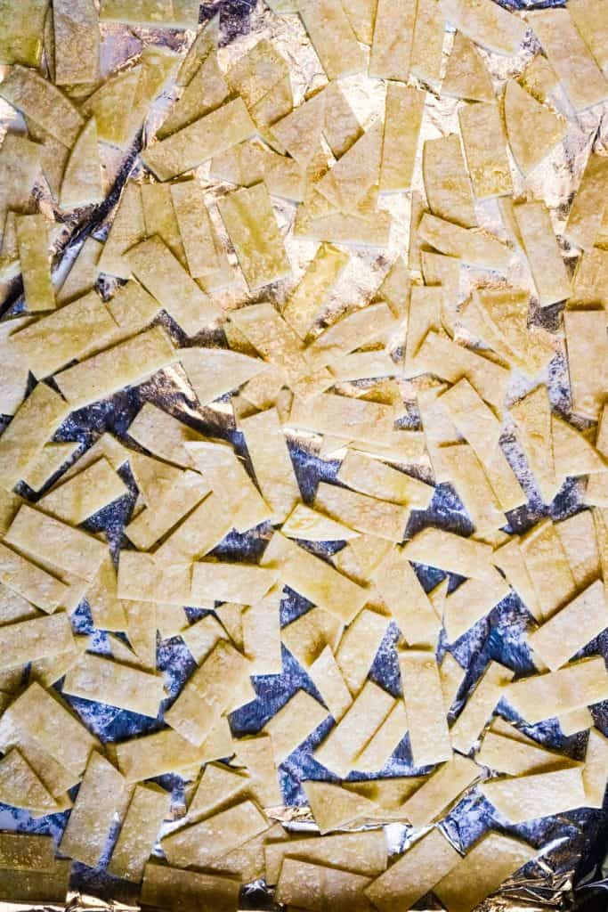 tortilla strips on a baking sheet ready to be baked