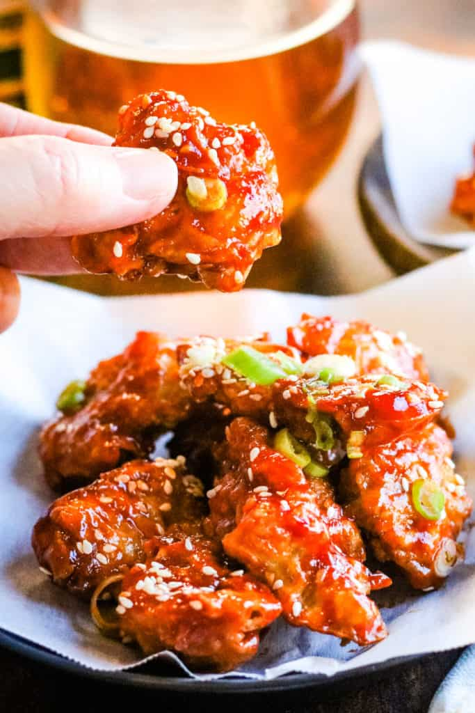 vetical shot of air fryer chicken in gochujang sauce with a hand lifting a piece